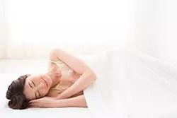 タオルケットで寝る女性