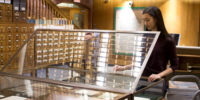 A student curates items on display in an exhibition about College Girl Fiction.