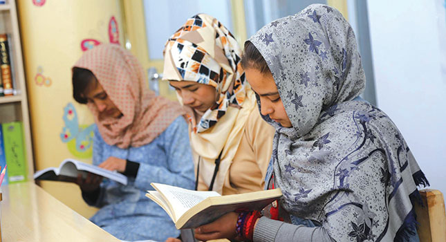 Three girls with heads covered in patterned cloth read books