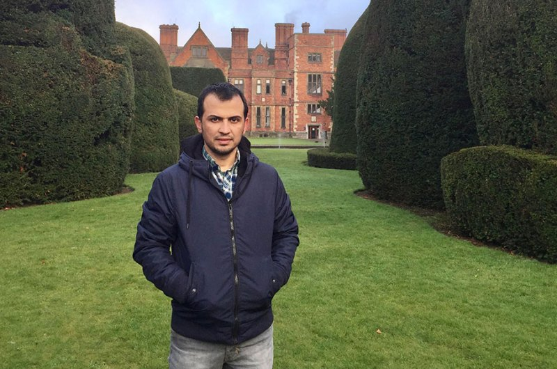 Adil stood infront of Heslington Hall, surrounded by bushes in the Quiet Place.