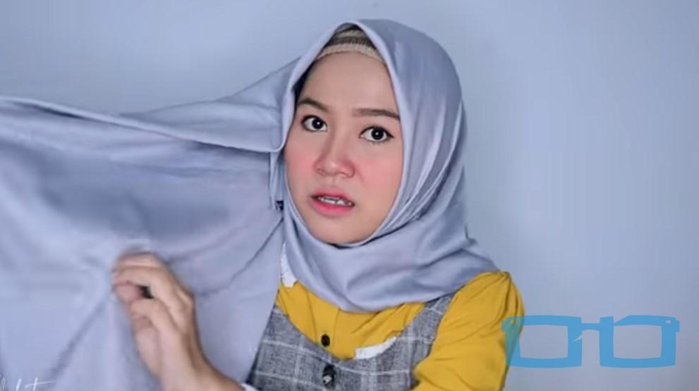 Tutorial Hijab Segi Empat Menutup Dada Syari untuk Wajah Bulat Ambil Bagian Tengah Sisi Hijab yang Panjang