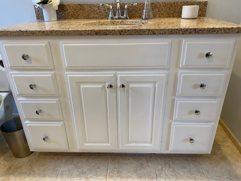 A white bathroom vanity cabinet with a brown granite countertop.
