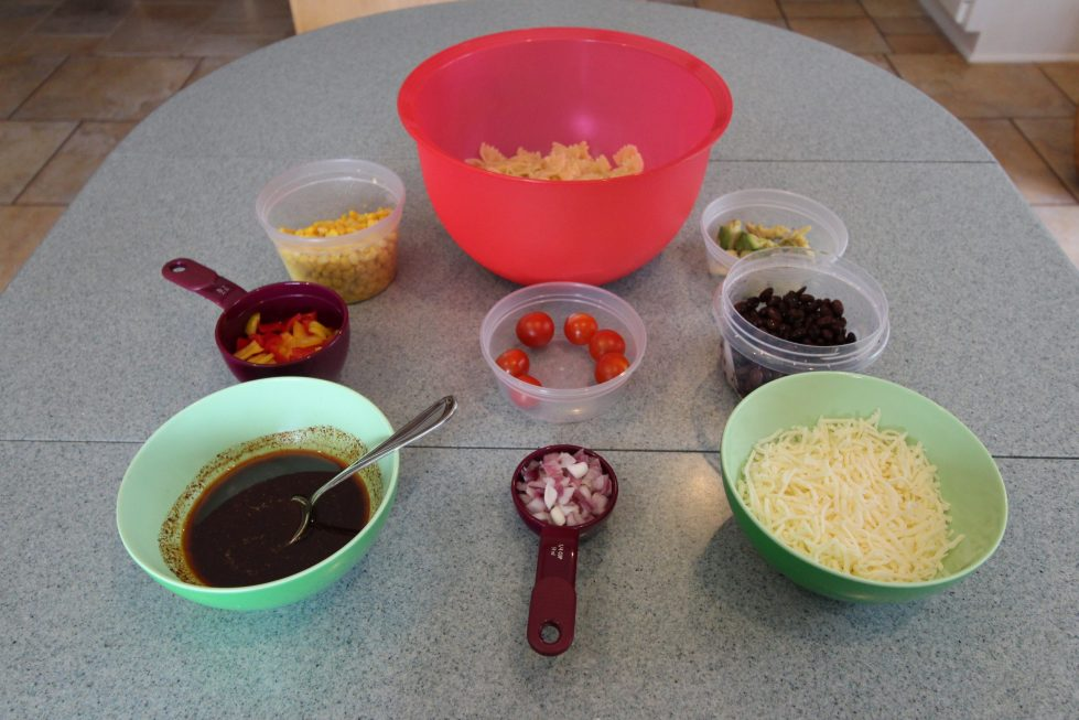 Bowls of ingredients for a pasta salad laid out on a table.