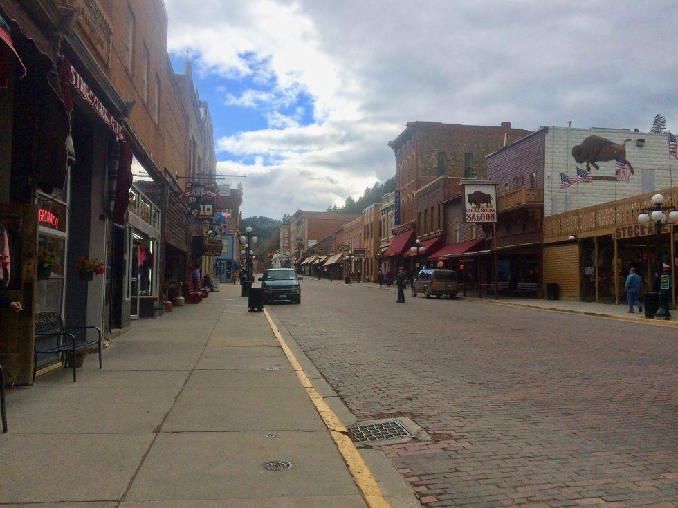 Main street in Deadwood, South Dakota, with people walking down the street near a saloon.