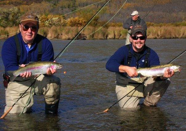 Three men fly fishing in Alaska. Two holding large Rainbow trout