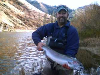 A fly fisherman holding a large steelhead on the Grande Ronde river