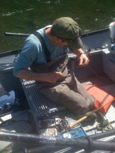 A fly fisherman in simms waders sitting on the rowing seat of a drift boat tying on a fly to his leader.