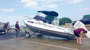 A boat that has slid off of its trailer on a boat ramp