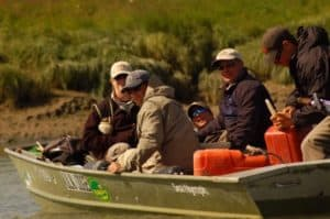 A guide refueling his boat while his fly fishermen for the day relive their experiences