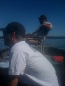 Two men sitting in chairs in a boat fly fishing