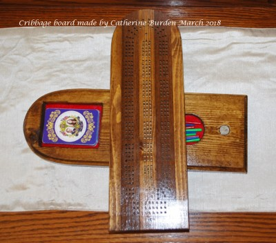 After being stained, Cribbage board with pegs and a deck of cards.