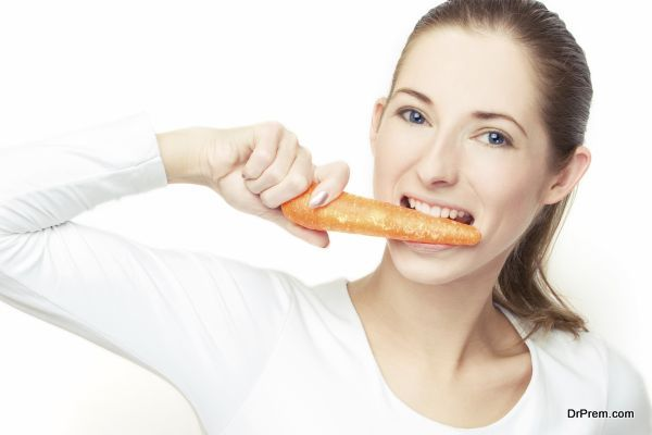 young woman eating the carrot, over white background