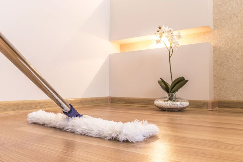 mop cleaning wooden floor in house