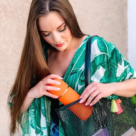 Vejo review - personal pod blender for smoothies - girl holding orange blender