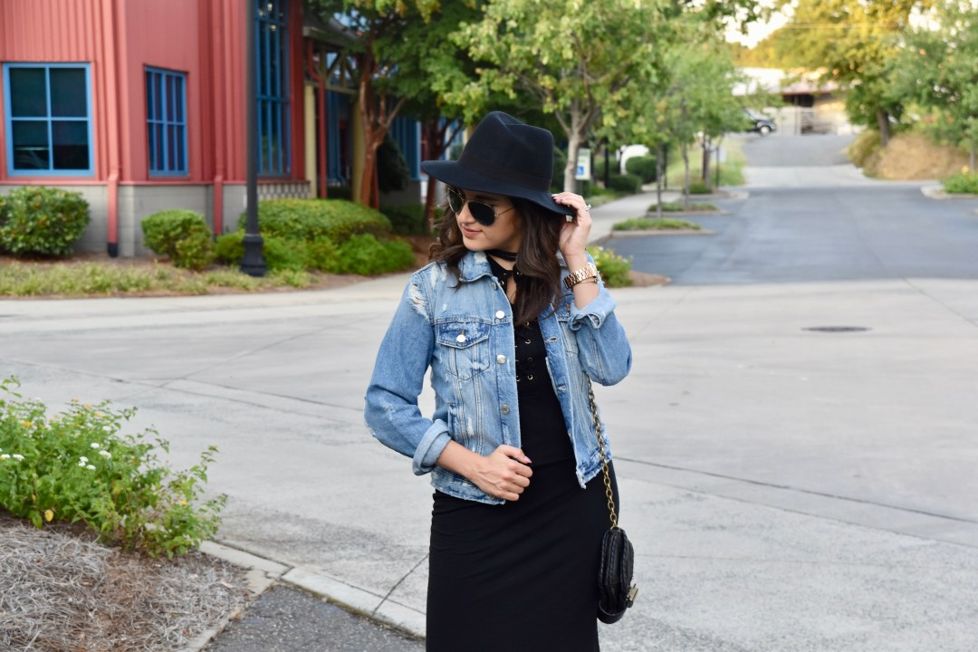 Dania outfit post in black dress, superga, jean jacket, and hat looking down