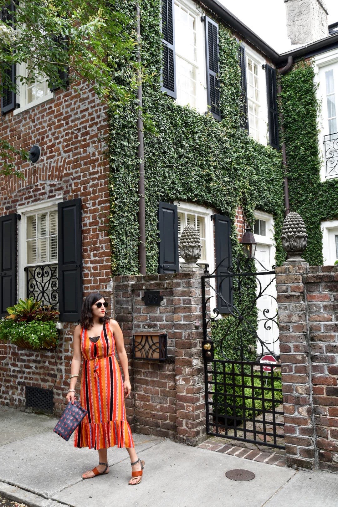 Aya wearing Elsa Fine dress Charleston SC in front of building covered in greenery