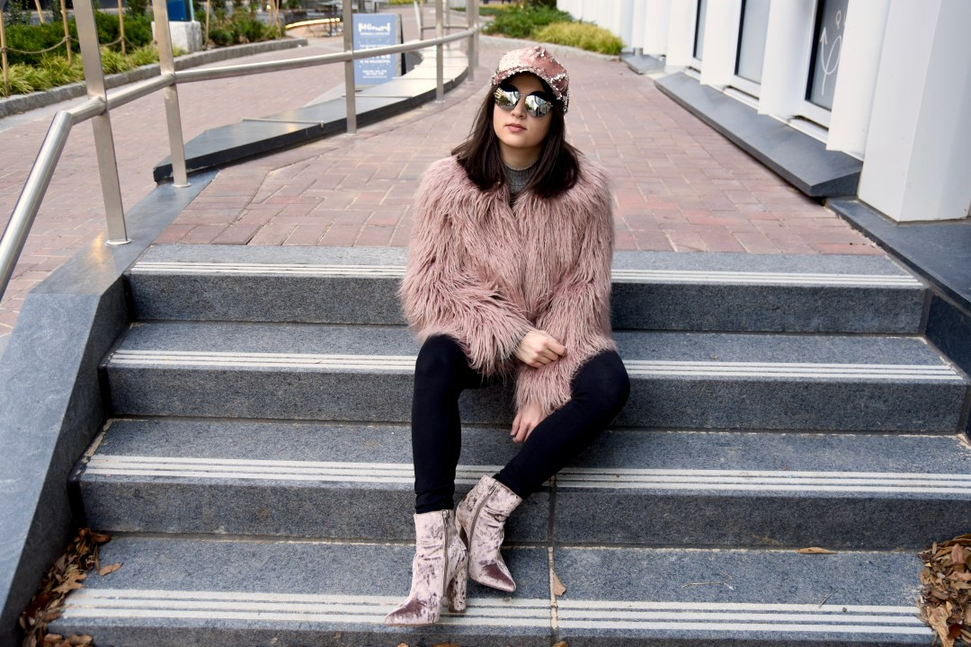 Dania sitting in Vince Camuto pink faux fur and jessica simpson boots in blush