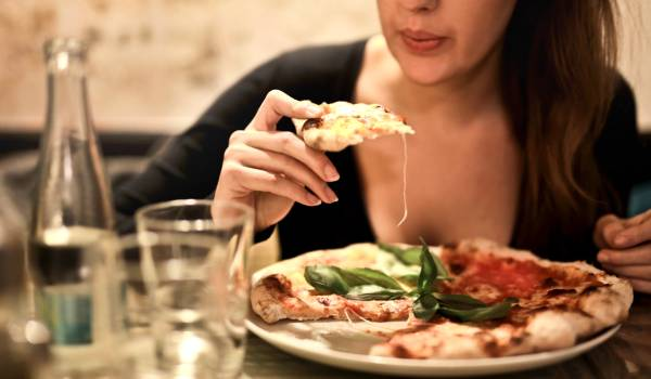 woman eating italian pizza with string cheese