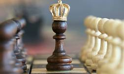 queen chess piece on chess board with little golden crown