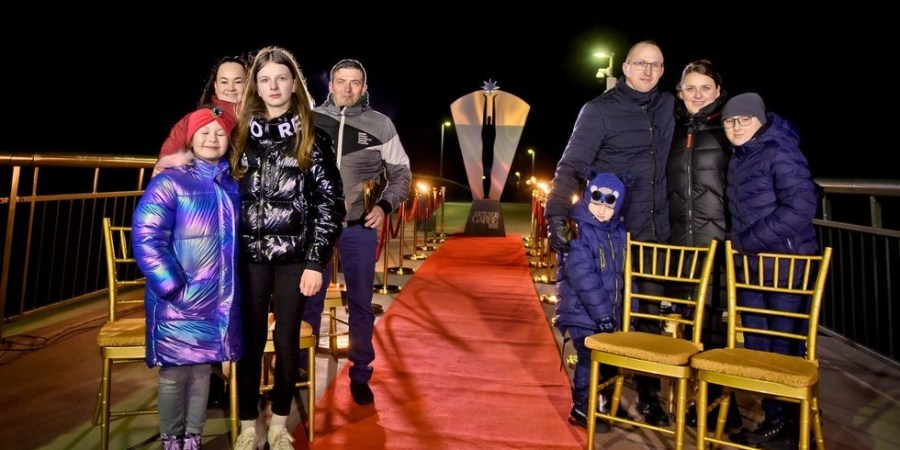 Gyvybę mažiesiems alytiškiams išgelbėjusieji V. Buinauskas (kairėje) ir N. Stanevičius su šeimomis padėkos vakare ant pėsčiųjų ir dviratininkų tilto Alytuje. TV3 nuotr.