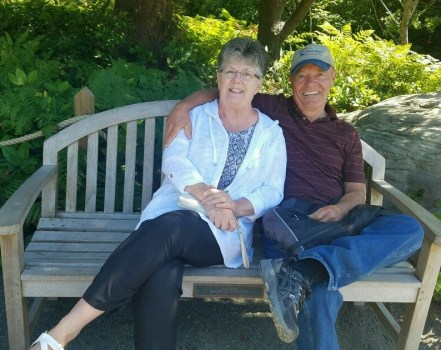 Pat and her husband sit together on a bench smiling