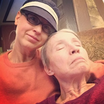 An older woman sleeps on the shoulder of a younfgr woman
