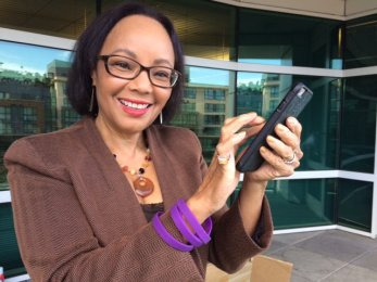 A woman smiling with her phone