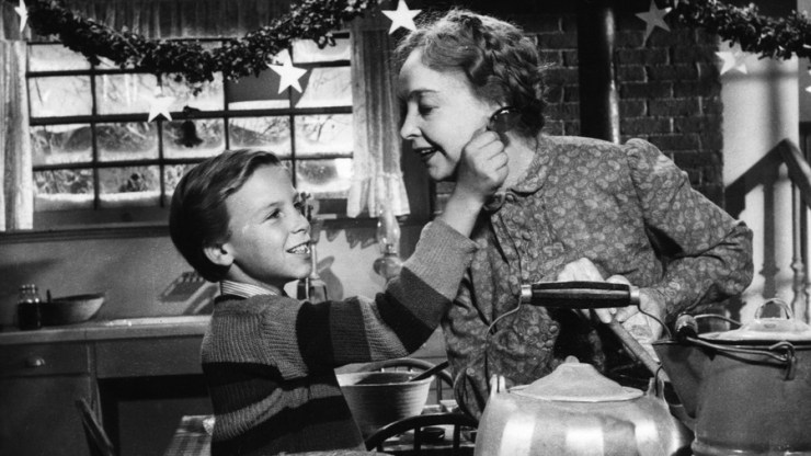 A still from Night of the Hunter featuring a boy and an older woman cooking together with Christmas decorations in the background
