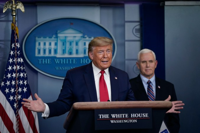 Donald Trump speaks as Vice President Mike Pence looks on during a briefing on the coronavirus pandemic in the press briefing room of the White House