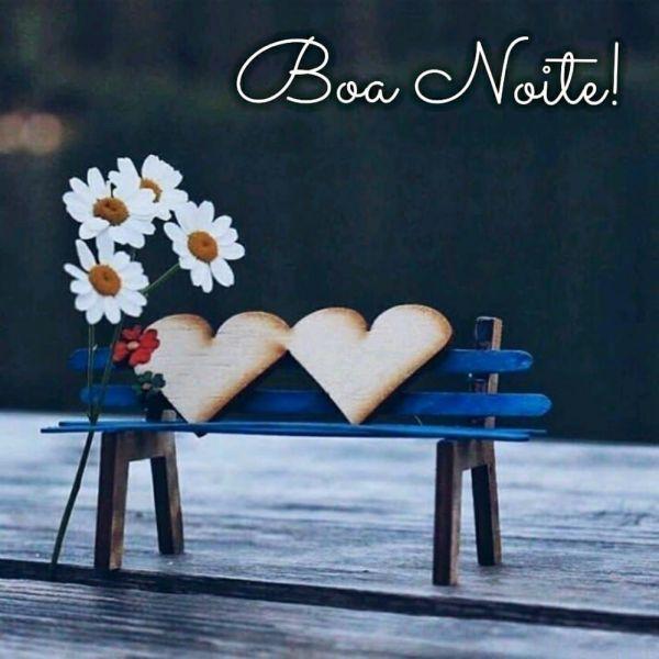 banquinho de praça com almofadas de corações e florea