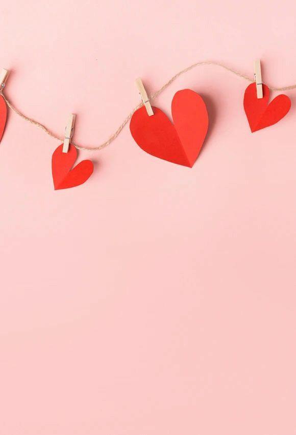 lindos corações no prendedor e fundo rosa