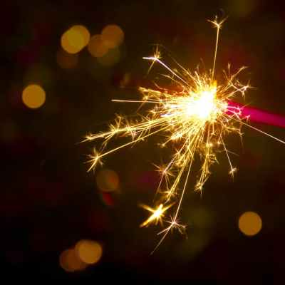 A lit sparkler with a pink handle emits light against a dark background.