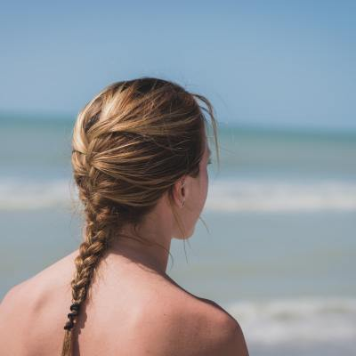 A brunette woman with a french braid hairstyle staring out into the ocean on a sunny day.