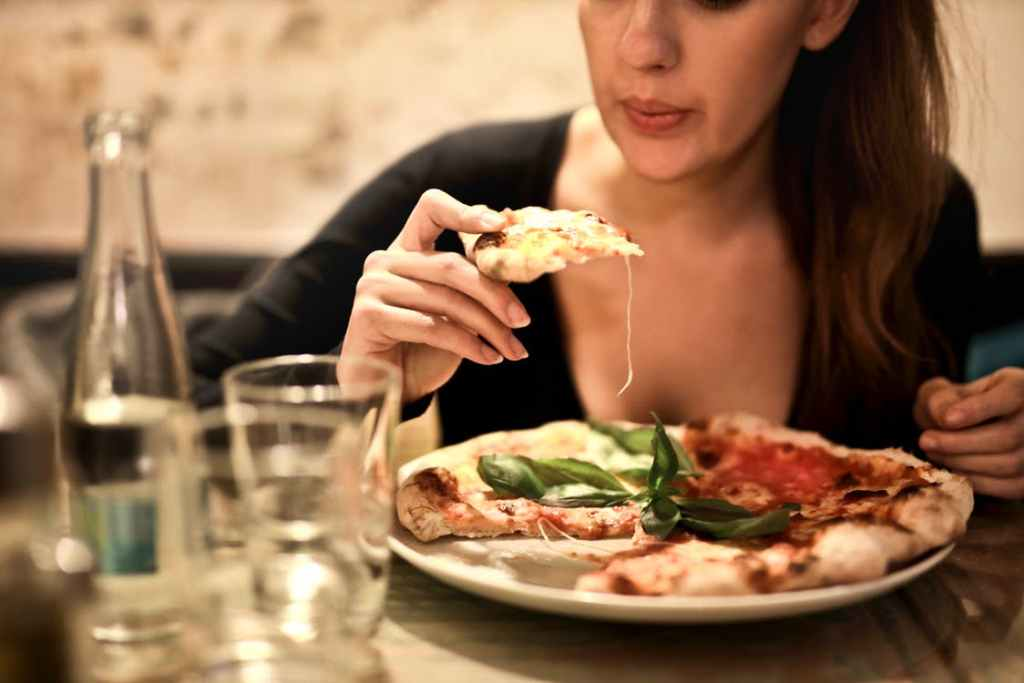 A woman sits at a table, eating pizza, practicing mindfulness.