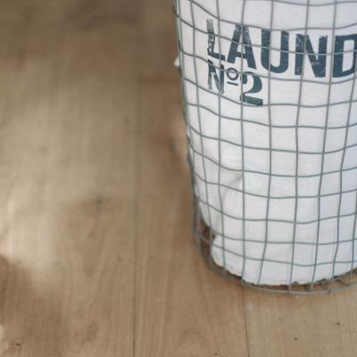 A wire laundry basket with a white lining sitting on a hardwood floor, with the words laundry number two printed on it.