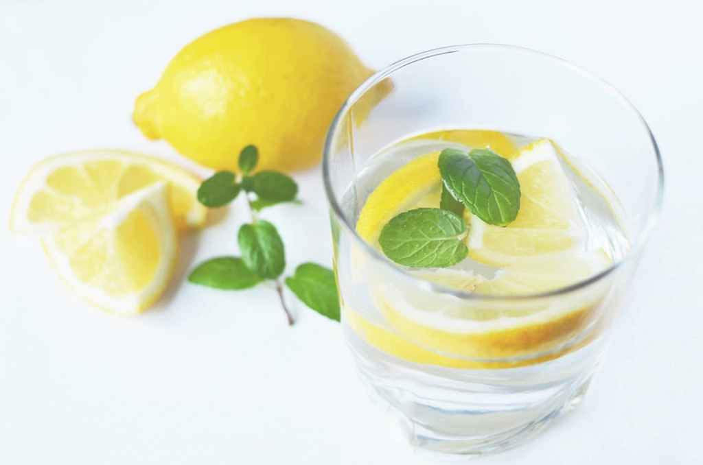 A glass of water with cut up lemons and mint floating in it, set on a white table.