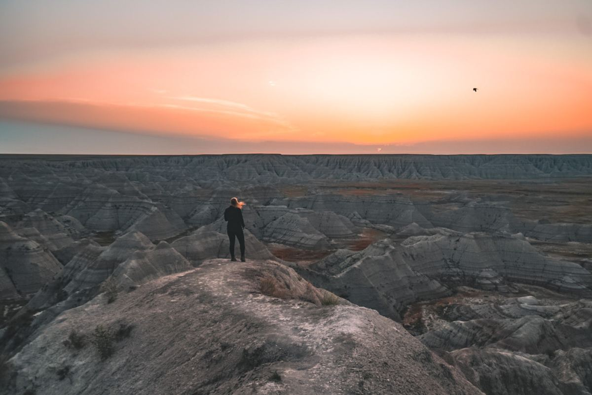 Woman standing near Badlands at sunrise 2