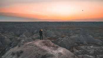 Woman standing near Badlands at sunrise 2