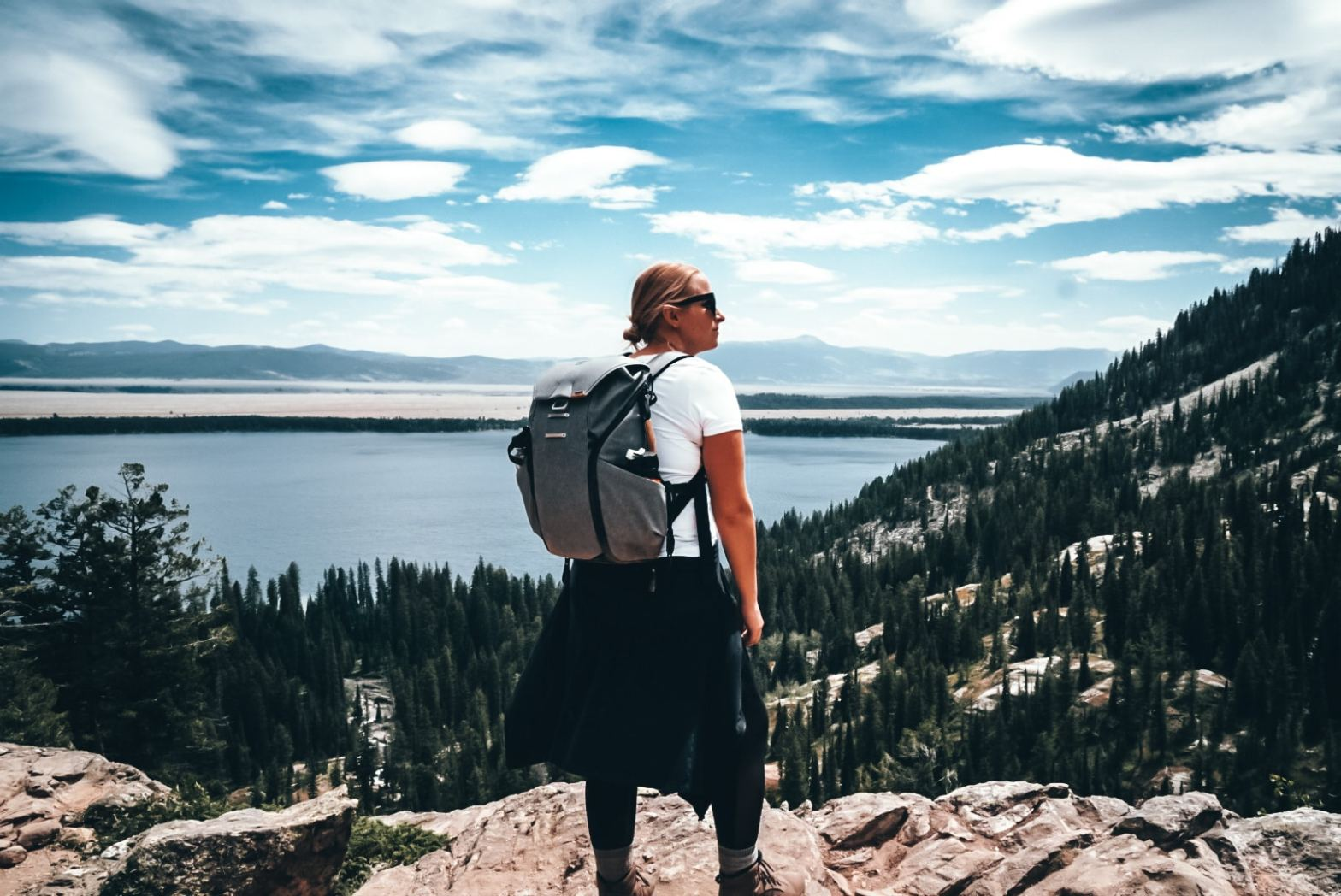 Hiking woman wearing backpack on Inspiration Point, Grand TEton