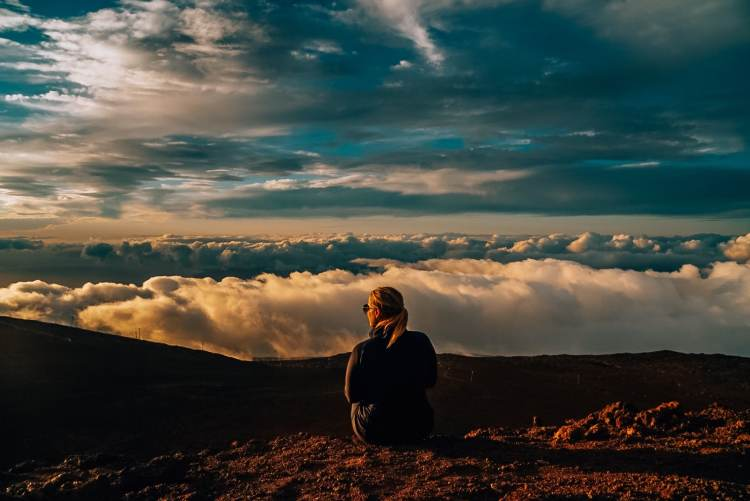 Woman sitting on the edge at sunset over the clouds