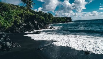 View from on the sand of a black sand beach out to the water