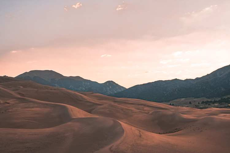 View of the Great Sand Dunes facing the mountains during sunrise with the sky pastel purple, pink, and yellow