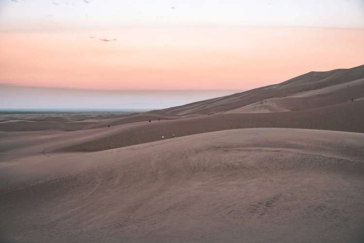 View of people on the Great Sand Dunes during sunrise with the sky pastel purple, pink, and yellow