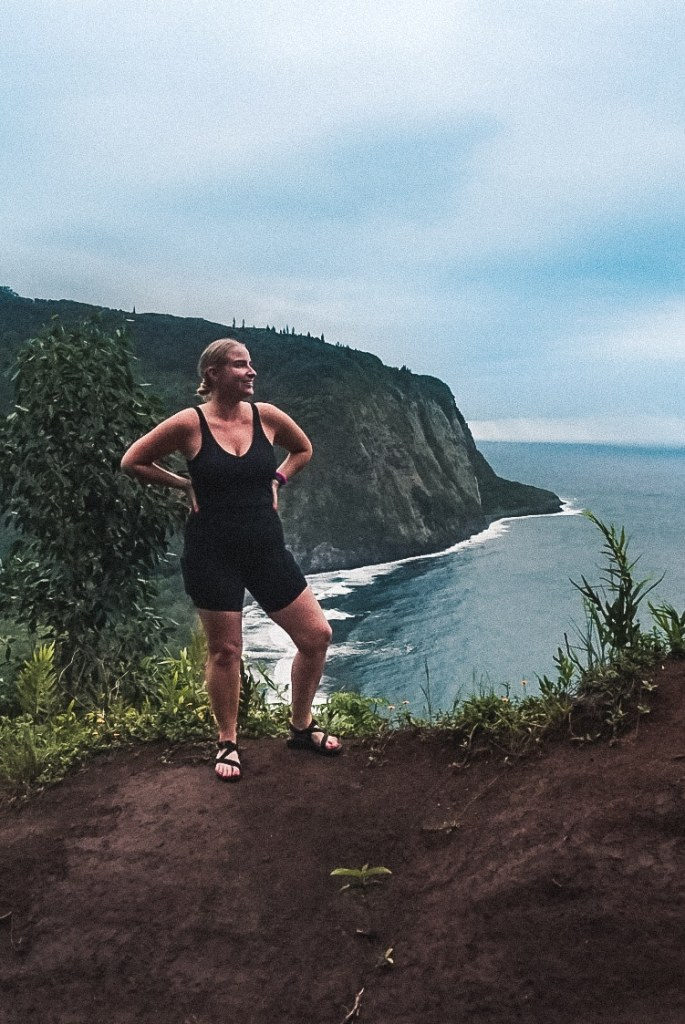 Woman in exercise tank top, shorts, and sandals standing in front of Waipio Valley from high up