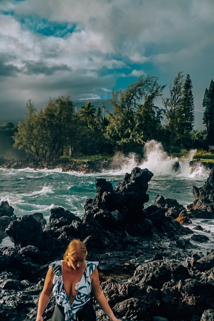 Woman walking along the black lava rock that is the coastline in the Ke'enae Peninsula with the water crashing against the coastline in the background