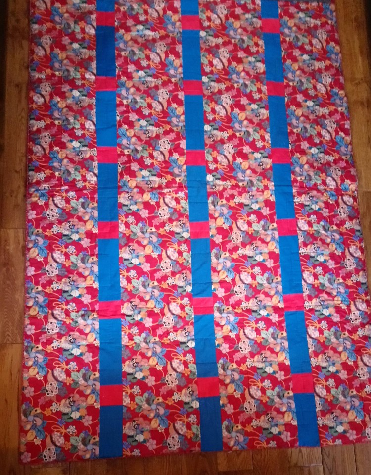 Photo of a quilt to show how inserting strips adds to the width