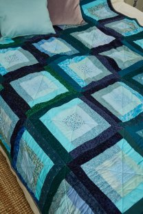 Detail of a blue and green quilt by Amanda Jane Ogden, using a modern version of log cabin blocks
