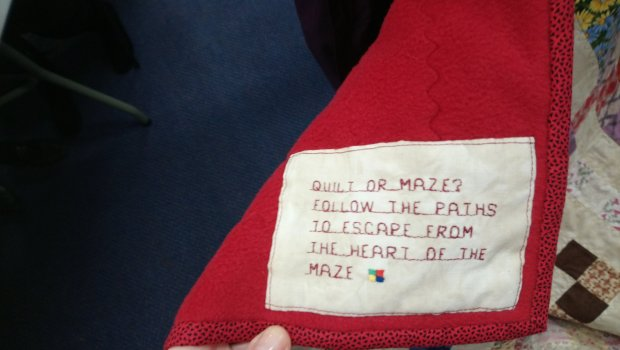 a quilt label explaining that the quilt is a puzzle maze