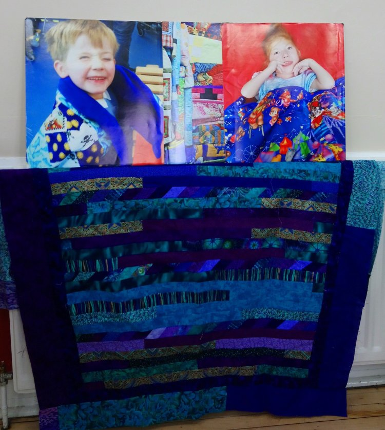 a quilt top with photos of recipients of Linus Quilts behind