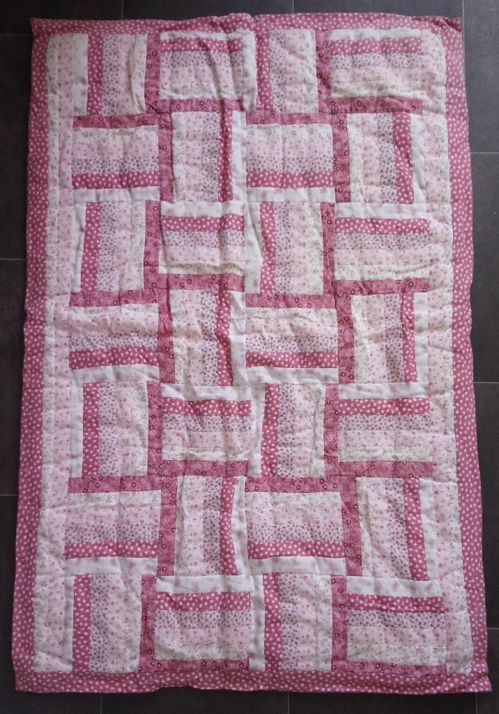 reverse of a quilt showing strip-pieced blocks